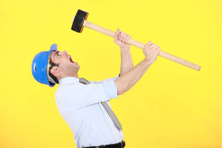 choleric: angry businessman holding a hammer Stock Photo