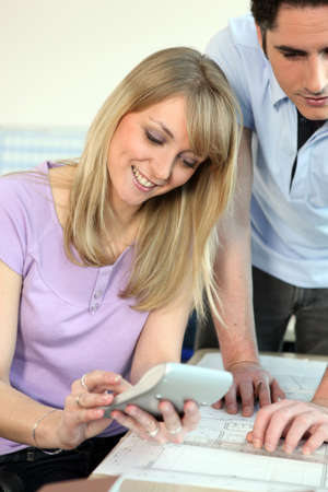 Young couple with architect plans and a calculator Stock Photo - 10855010
