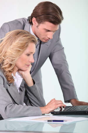 collaborators: businessman and businesswoman looking at laptop Stock Photo