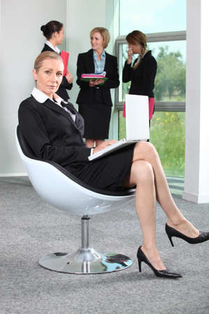Businesswoman sat in chair with colleagues in background Stock Photo - 10854356