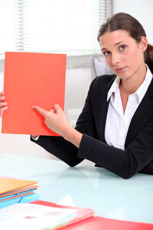 Brunette businesswoman pointing to a file left blank for your image photo