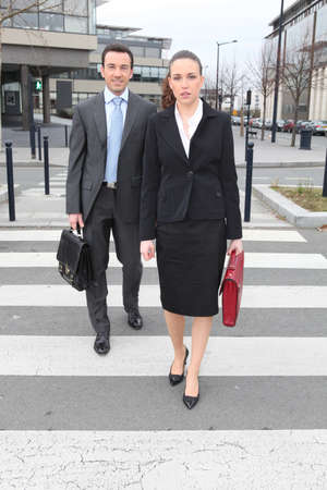 business briefcase: Businessman and woman crossing the street