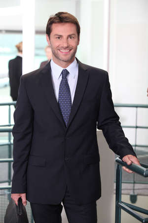 Smiling business man standing in an office building photo