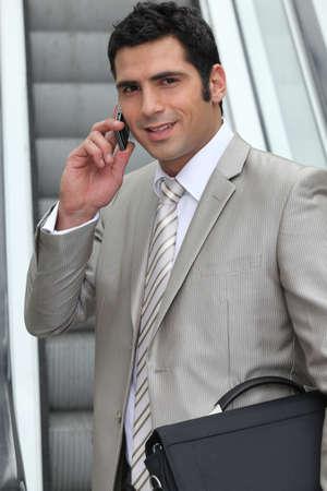 telephone salesman: Man using a cellphone at the  bottom of an escalator