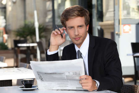 expresso: Young executive reading a newspaper in a cafe