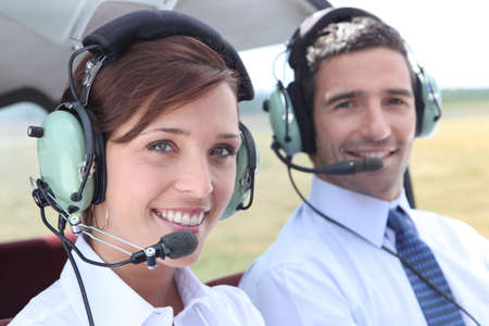 Man and woman wearing headsets in the open cockpit of a light aircraft photo