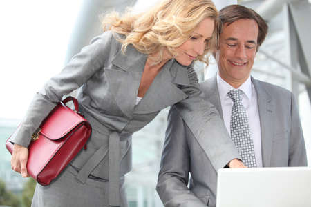 45 55 years: Business couple looking at laptop Stock Photo