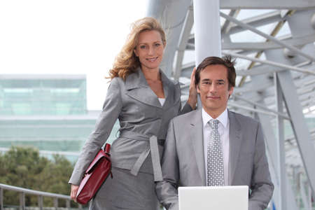 Business man sat with laptop next to female colleague photo