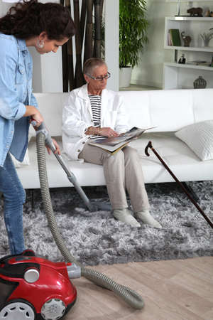 a young woman vacuuming at a senior woman Stok Fotoğraf