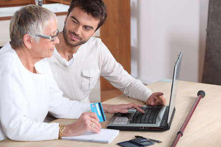Young man helping senior woman buy online photo