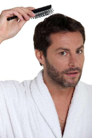 combing: Man in a toweling robe brushing his hair Stock Photo