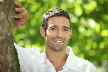 man front view: Smiling man leaning against a tree trunk