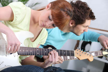 Young couple tuning and playing guitar Stock Photo - 10855003