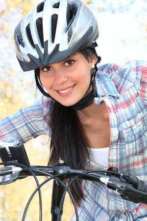 firmness: una mujer joven que monta en bicicleta en el parque Foto de archivo