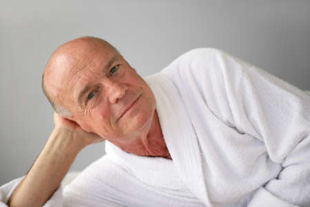 65 years old: Elderly man lying in his bathrobe