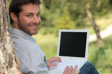 40 45: Man on laptop outside Stock Photo