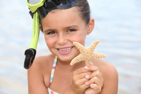 Little girl at the beach holding star fish photo