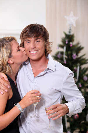 Young woman kissing her boyfriend at Christmas Stock Photo - 10854270