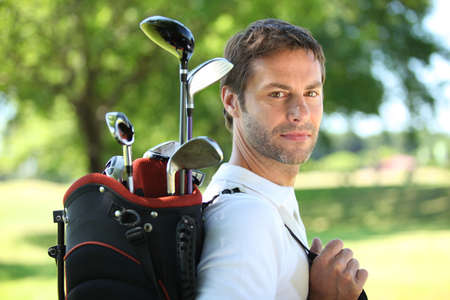 Golfer carrying clubs photo
