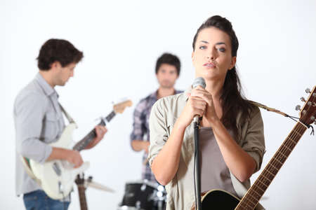 a rehearsal: a guitar player, a drummer and a female singer