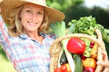 Donna con un cesto di partecipazione cappello di paglia di verdure.