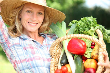market gardener: Woman with a straw hat holding basket of vegetables. Stock Photo