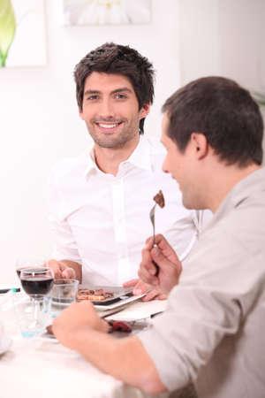 hombres gays: Amigos con una comida juntos Foto de archivo