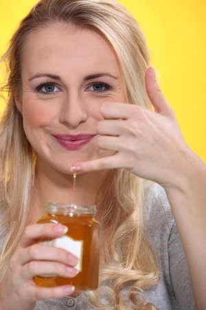 honey blonde: Smiling woman holding a honeypot