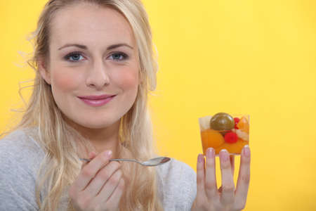 front raise: Blond woman holding fruit salad