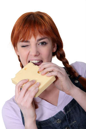 Woman biting into block of cheese photo