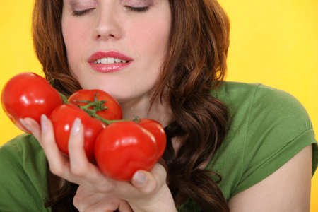tantalizing: Woman smelling vine tomatoes