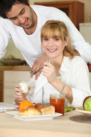 Woman eating breakfast while her affectionate boyfriend gazes at her Stock Photo - 10854601