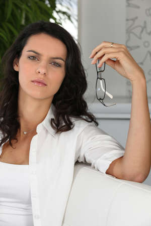 oculist: Woman holding pair of glasses