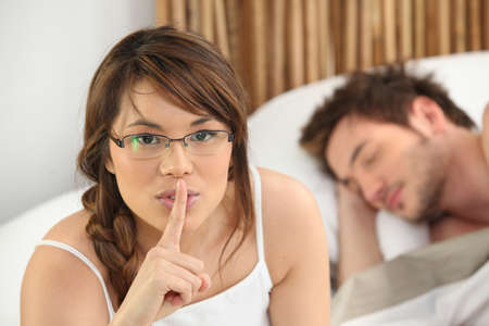intrusive: Woman telling you to be quiet while her lover sleeps Stock Photo