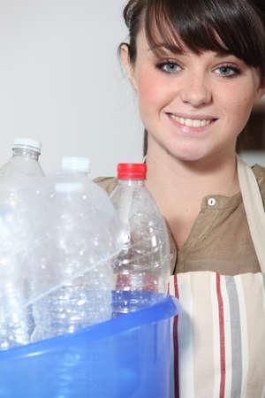 Young woman recycling empty plastic bottles Stock Photo - 10853463