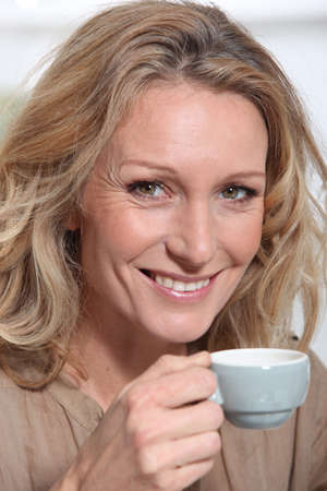 mature blonde woman  with a cup of coffee photo