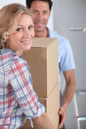 removals: Couple carrying packing boxes into new home
