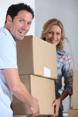 Couple moving a pile of large cardboard boxes photo