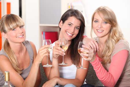 Three female friends drinking wine on sofa photo