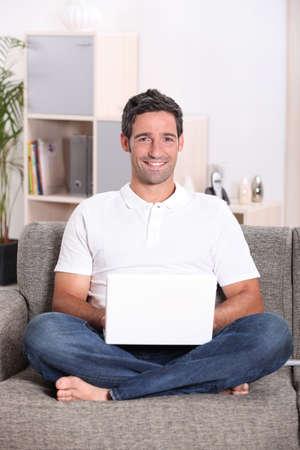 Man sat at home using laptop computer photo