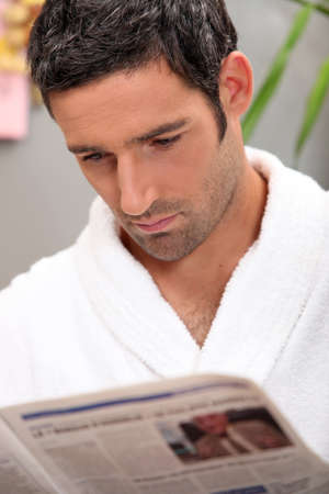Handsome man in a toweling robe reading a journal photo
