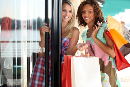 shopping girl: portrait of two girls with shopping bags