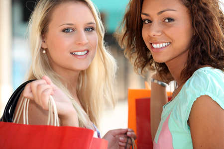 metis: two 20 years old girls, a blonde and a metis doing shopping