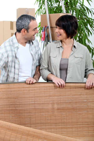 Couple unrolling a mat in their new home Stock Photo - 10855077