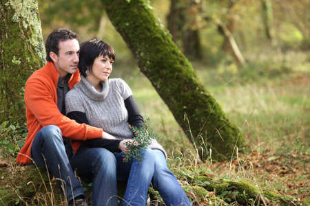 Couple sitting in woods photo