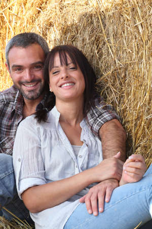 all smiles: couple of farmers all smiles posing in barn Stock Photo