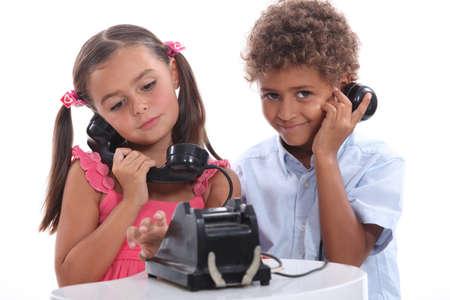 niños platicando: Niño y niña con teléfono antigua