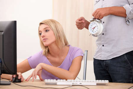 a young blonde woman is doing computer and a man is showing an alarm clock