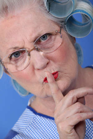 frowning: Elderly woman with her hair in rollers holding her finger up to her lips Stock Photo