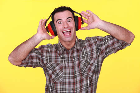 electrify: happy man wearing earmuffs cancelling noise